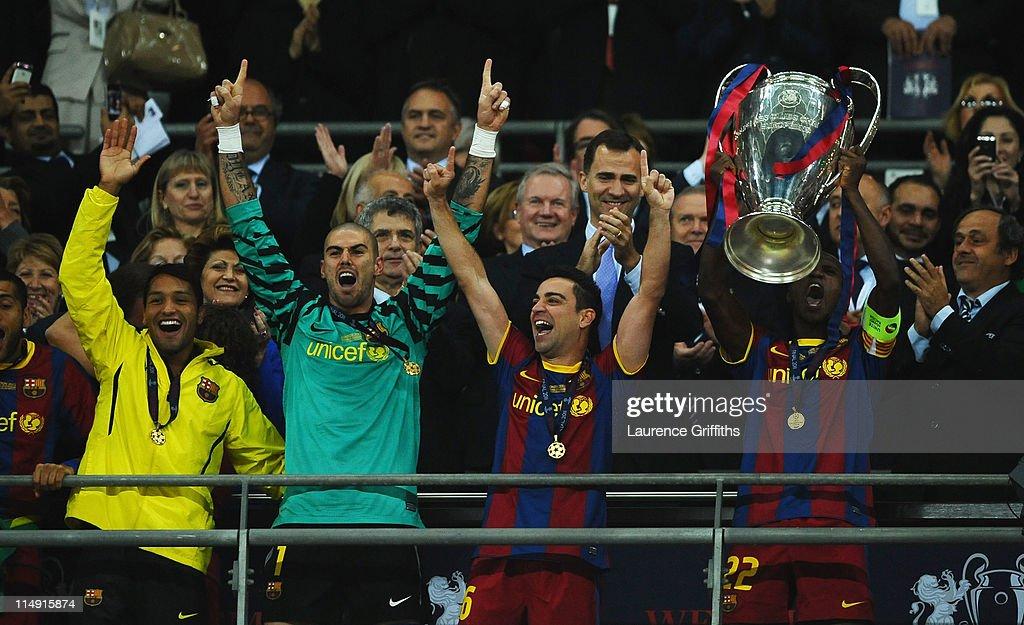 Prince Filipe of Spain applauds as Eric Abidal (R) of FC Barcelona lifts the trophy and celebrates with teammates Victor Valdes (2L) and Xavi (2R) after victory in the UEFA Champions League final between FC Barcelona and Manchester United FC at Wembley Stadium on May 28, 2011 in London, England.