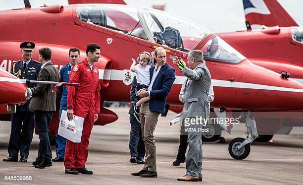 Prince George is carried by his father Prince William, Duke of Cambridge as they meet members of the red arrows during a visit to the Royal...