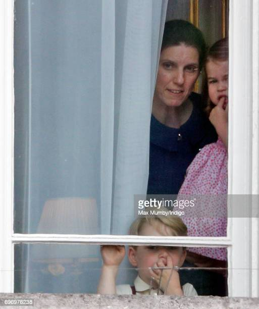 Prince George of Cambridge and Princess Charlotte of Cambridge accompanied by their nanny Maria Teresa Borrallo watch from a window of Buckingham...