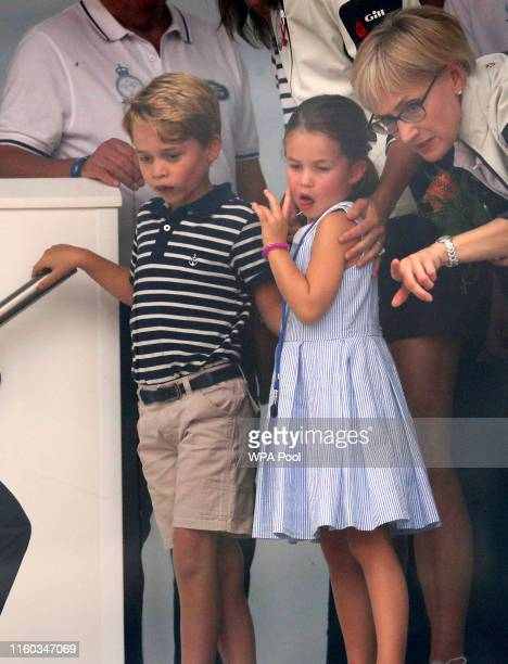 Prince George of Cambridge and Princess Charlotte of Cambridge look through a window at the prize giving after the King's Cup regatta on August 8,...