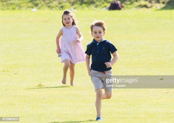 Prince George of Cambridge and Princess Charlotte of Cambridge run together during the Maserati Royal Charity Polo Trophy at Beaufort Park on June 10...