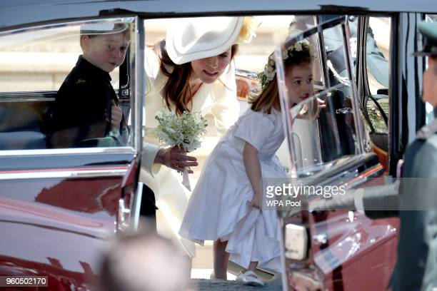 Prince George of Cambridge and Princess Charlotte of Cambridge step inside their car with their mother Catherine Duchess of Cambridge as they leave...