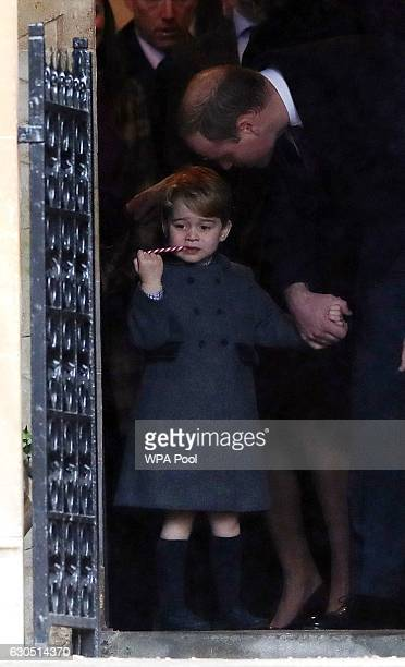 Prince George of Cambridge eats a sweet as he leave following the service at St Mark's Church on Christmas Day on December 25 2016 in Bucklebury...