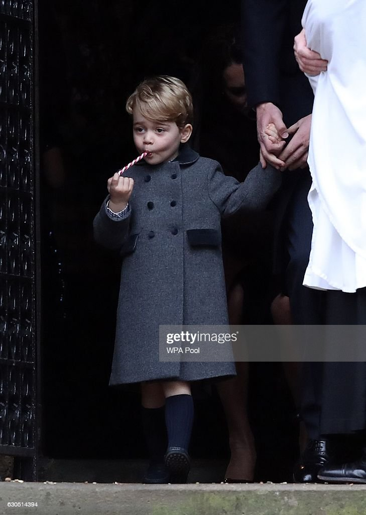 Prince George of Cambridge eats a sweet as he leaves following the service at St Mark's Church on Christmas Day on December 25, 2016 in Bucklebury, Berkshire.