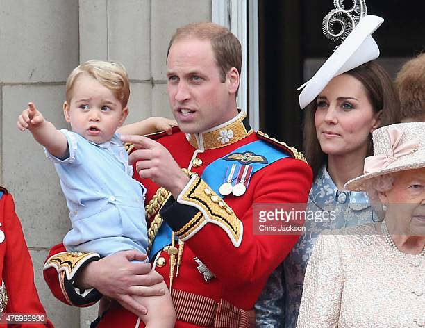 Prince George of Cambridge is held by Prince William Duke of Cambridge as Catherine Duchess of Cambridge looks on from the balcony of Buckingham...