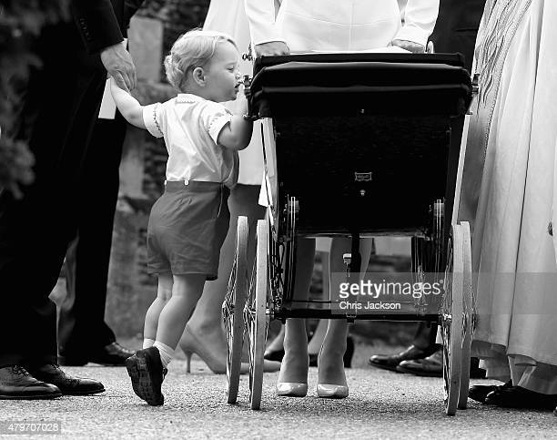 Prince George of Cambridge looks at his sister Princess Charlotte of Cambridge in her pram as he leaves the Church of St Mary Magdalene on the...