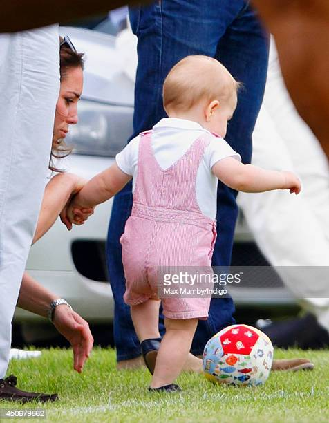 Prince George of Cambridge plays with a football whilst holding his mother Catherine, Duchess of Cambridge's hand as they watch Prince William, Duke...
