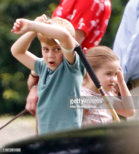 Prince George of Cambridge plays with a polo mallet as he and Princess Charlotte of Cambridge attend the King Power Royal Charity Polo Match in which...