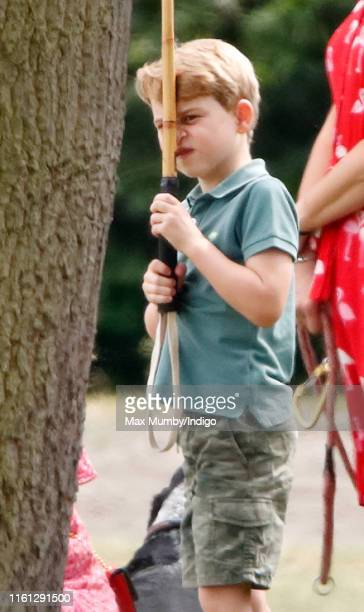Prince George of Cambridge plays with a polo mallet as he attends the King Power Royal Charity Polo Match in which Prince William Duke of Cambridge...
