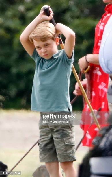 Prince George of Cambridge plays with a polo mallet as he attends the King Power Royal Charity Polo Match, in which Prince William, Duke of Cambridge...