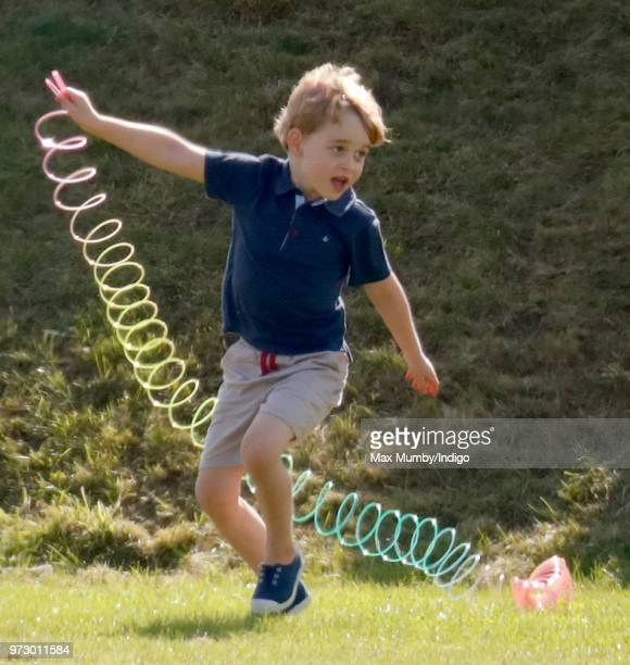 Prince George of Cambridge plays with a Slinky toy as he attends the Maserati Royal Charity Polo Trophy at the Beaufort Polo Club on June 10 2018 in...