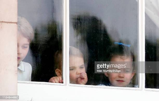 Prince George of Cambridge, Prince Louis of Cambridge and Princess Charlotte of Cambridge look out of a window of Buckingham Palace as they attend...