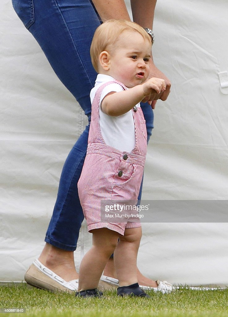 Prince George of Cambridge walks alongside his mother Catherine, Duchess of Cambridge as they watch Prince William, Duke of Cambridge & Prince Harry play in the Jerudong Trophy charity polo match at Cirencester Park Polo Club on June 15, 2014 in Cirencester, England.