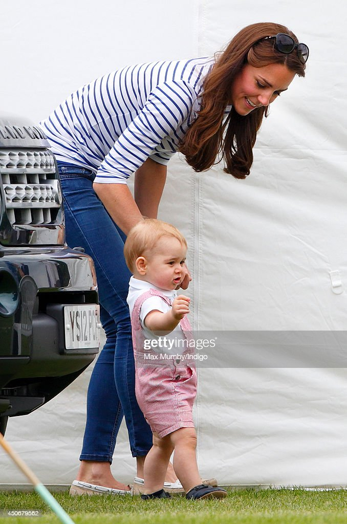 Prince George of Cambridge walks holding his mother Catherine, Duchess of Cambridge's hand as they watch Prince William, Duke of Cambridge & Prince Harry play in the Jerudong Trophy charity polo match at Cirencester Park Polo Club on June 15, 2014 in Cirencester, England.