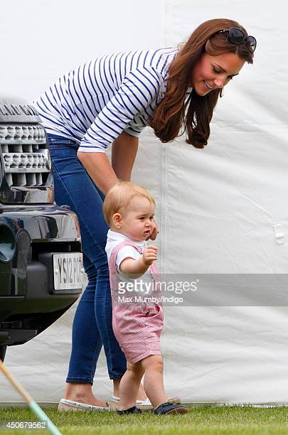 Prince George of Cambridge walks holding his mother Catherine Duchess of Cambridge's hand as they watch Prince William Duke of Cambridge Prince Harry...