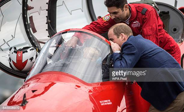 Prince George sits in the cockpit of a red arrows aircraft as his father Prince William, Duke of Cambridge looks on during a visit to the Royal...