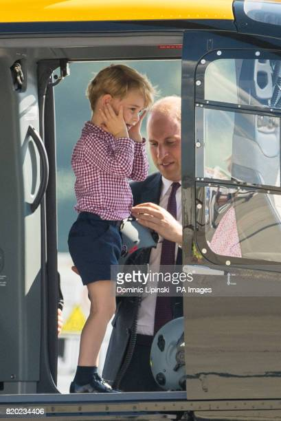 Prince George stands in a rescue helicopter as his father the Duke of Cambridge adjusts a helmet for him to wear during a visit to Airbus in Hamburg...