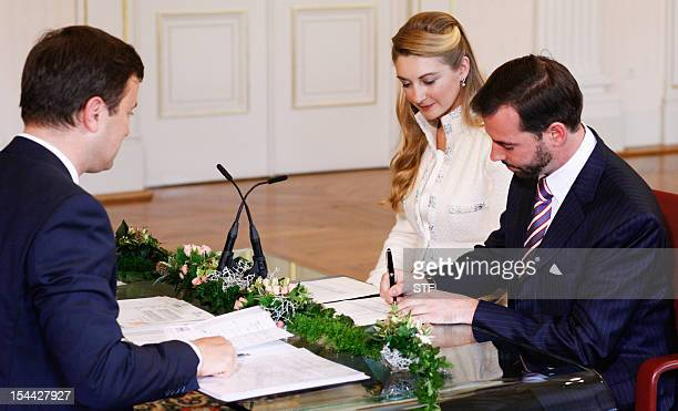 Prince Guillaume, heir to the thrown of Luxembourg, and Belgium's Countess Stephanie de Lannoy sign documents in front of Luxembourg city mayor...