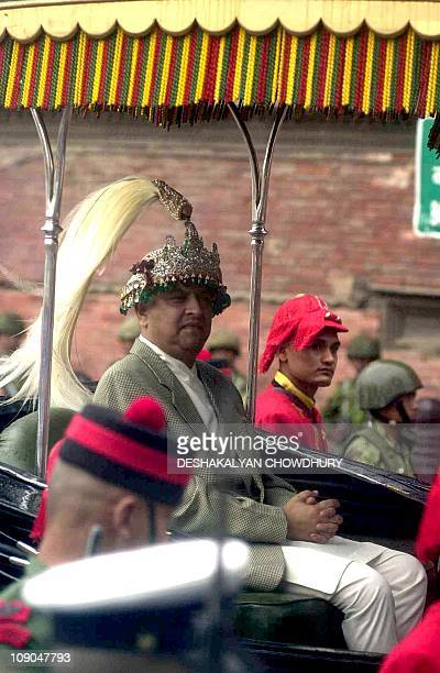 Prince Gyanendra is escorted by security guards after his swearingin ceremony at Hanuman Dhoka temple where he was crowned the new King of Nepal in...