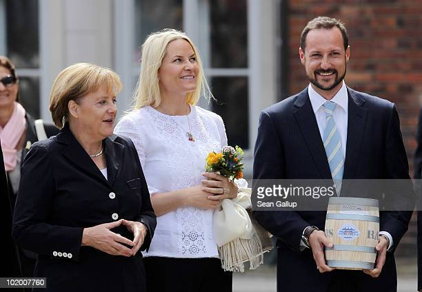 Prince Haakon of Norway holds a barrell of marinated herring as Princess Mette-Marit of Norway and German Chancellor Angela Merkel look on upon their...