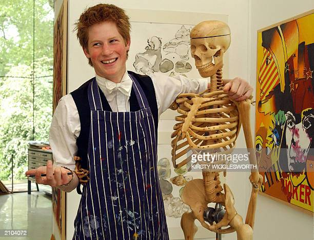 Prince Harry a keen artist and the younger son of the Prince of Wales poses 12 May 2003 next to a skeleton in Eton College's Drawing School which was...