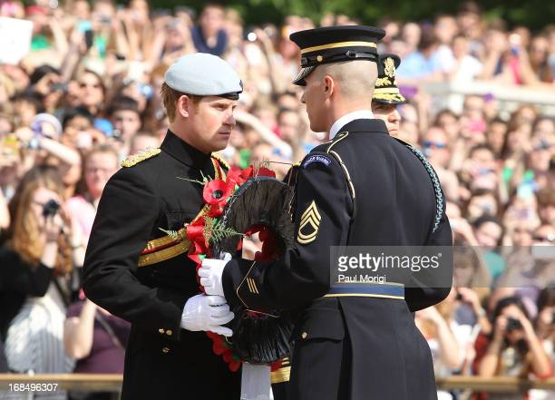 Prince Harry , accompanied by an honour guard, participates in a wreath laying ceremony during a visit to Arlington National Cemetery on the second...