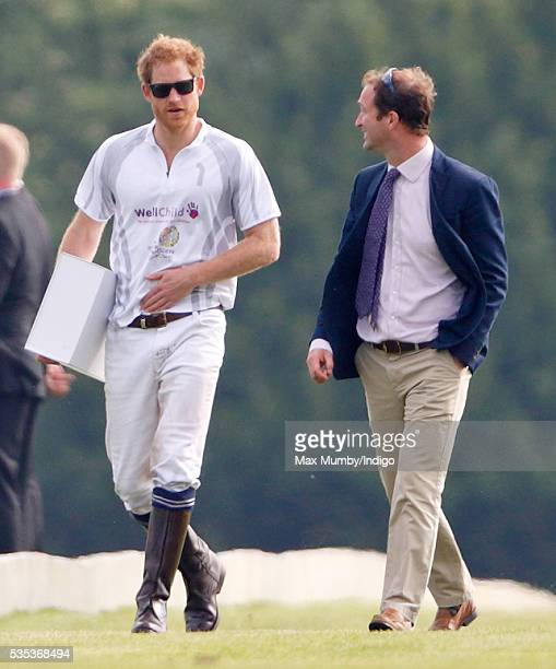 Prince Harry accompanied by his polo manager Andrew Tucker attends the Audi Polo Challenge at Coworth Park Polo Club on May 29 2016 in Ascot England