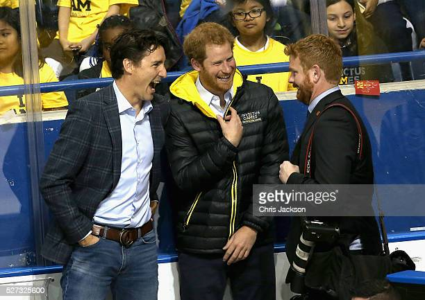 Prince Harry and Canadian Prime Minister Justin Trudeau joke with the Prime Minister's photographer as they watch a sledgehockey match Mattany at the...