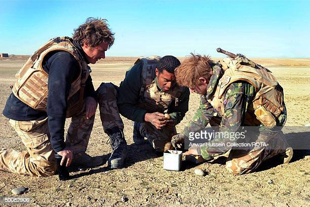 Prince Harry and his fellow soldiers prepare a breakfast of biscuits mixed with jam and butter in the desert on February 19 2008 in Helmand Province...