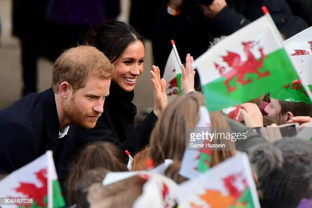 Prince Harry and his fiancee Meghan Markle shake hands with children as they arrive to a walkabout at Cardiff Castle on January 18 2018 in Cardiff...