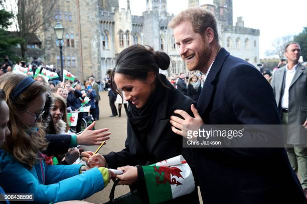 Prince Harry and his fiancee Meghan Markle sign autographs and shake hands with children as they arrive to a walkabout at Cardiff Castle on January...