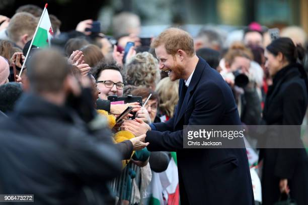 Prince Harry and his fiancee Meghan Markle sign autographs as they arrive to a walkabout at Cardiff Castle on January 18 2018 in Cardiff Wales