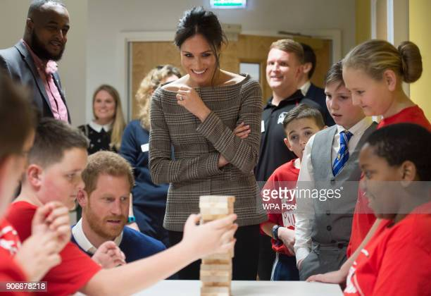 Prince Harry and his fiancee Meghan Markle watch a game of Jenga during their visit to Star Hub on January 18 2018 in Cardiff Wales