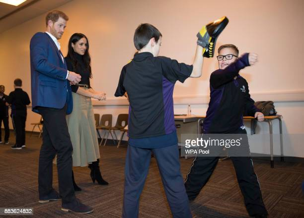 Prince Harry and his fiancee US actress Meghan Markle attend a Kick Boxing presentation during their visit to Nottingham Academy on December 1 2017...