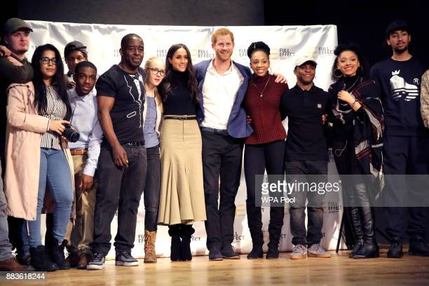 Prince Harry and his fiancee US actress Meghan Markle pose for a photograph with the cast and crew of a hip hop opera performed by young people...