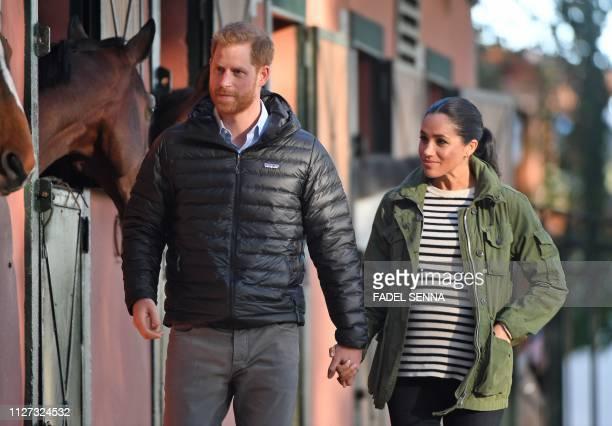 TOPSHOT Prince Harry and his wife Meghan Duke Duchess of Sussex arrive at the Moroccan Royal Federation of Equestrian Sports in Rabat on February 25...