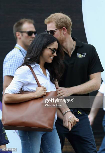 Prince Harry and Meghan Markle hold hands a Wheelchair Tennis match during the Invictus Games 2017 at Nathan Philips Square on September 25 2017 in...