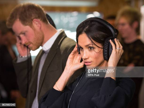 Prince Harry and Meghan Markle listen to a broadcast through headphones at Reprezent 1073FM in Pop Brixton on January 9 2018 in London England The...