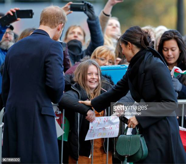 Prince Harry and Meghan Markle meet a girl holding a 'my name is Megan too' sign as they visit Cardiff Castle on January 18 2018 in Cardiff Wales