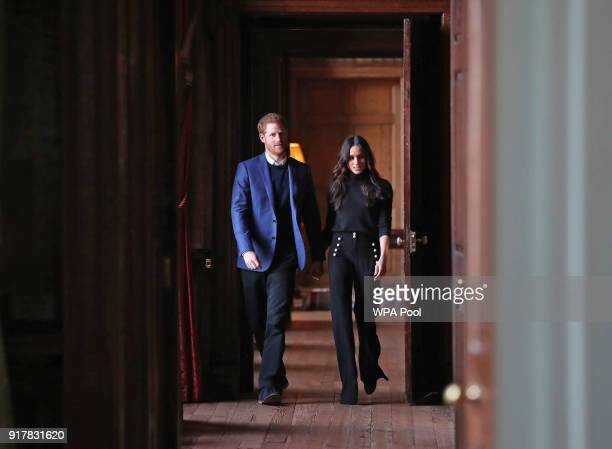 Prince Harry and Meghan Markle walk through the corridors of the Palace of Holyroodhouse on their way to a reception for young people at the Palace...