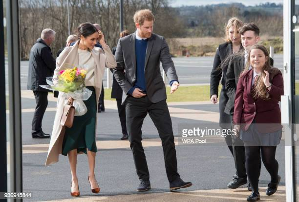 Prince Harry and Meghan Markle walk with student Amber Hamilton and Secretary of State for Northern Ireland Karen Bradley during their visit to the...
