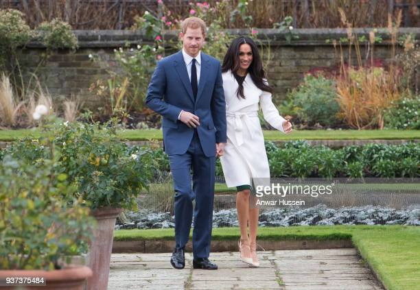 Prince Harry and Meghan Markle, wearing a white belted coat by Canadian brand Line The Label, attend a photocall in the Sunken Gardens at Kensington...