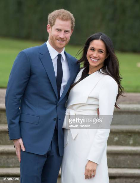 Prince Harry and Meghan Markle wearing a white belted coat by Canadian brand Line The Label attend a photocall in the Sunken Gardens at Kensington...