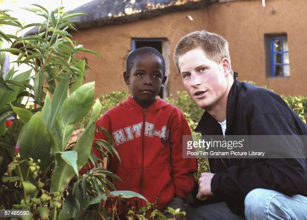 Prince Harry and Mutsu Potsane, inspect the Peach Tree that they planted in March 2004, in the grounds of the Mants'ase children's home, while on a...