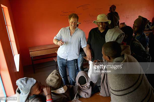 Prince Harry and Prince Seeiso of Lesotho share a joke with herd boys during a visit to a herd boy night school constructed by Sentebale on December...