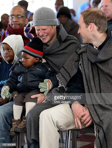 Prince Harry and Prince William clap as Prince Harry holds a young boy during a visit to a child education centre on June 17 2010 in Semonkong...