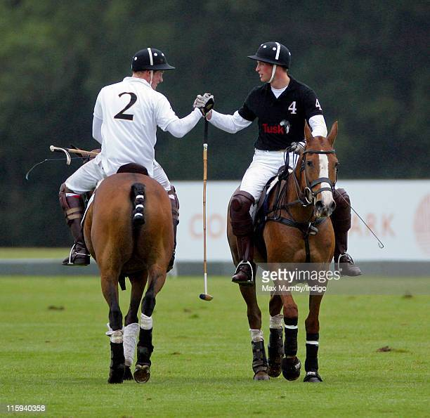 Prince Harry and Prince William Duke of Cambridge shake hands after competing against each other in the Sentebale Polo Cup polo match at Coworth Park...