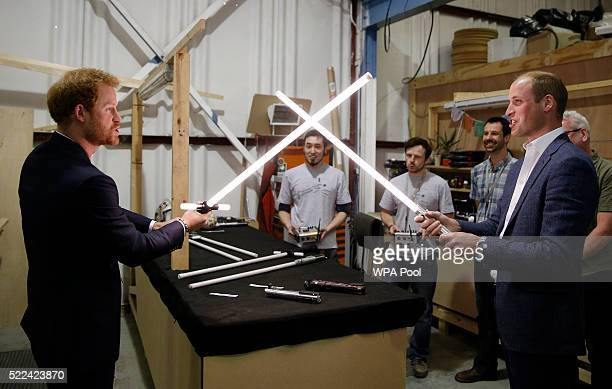 Prince Harry and Prince William Duke of Cambridge try out light sabres during a tour of the Star Wars sets at Pinewood studios on April 19 2016 in...