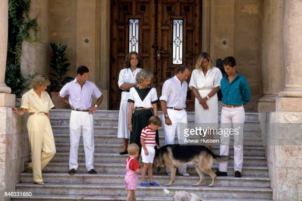 Prince William and Prince Harry play with a dog as they pose with Prince Charles Prince of Wales and Princess Diana Princess of Wales and the Spanish...