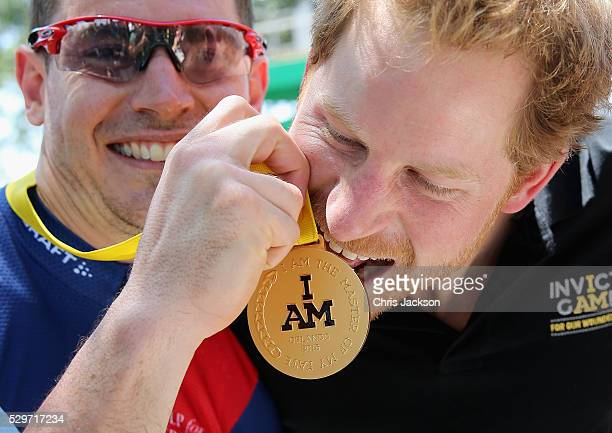 Prince Harry bites Jaco van Gass's gold medal at the road cycling event during the Invictus Games Orlando 2016 at ESPN Wide World of Sports on May 9...